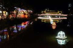 Ponte coberta sobre um rio pequeno, iluminação da noite, luzes de néon imagem de stock
