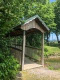 Ponte coperto di legno sopra la corrente al parco Immagini Stock