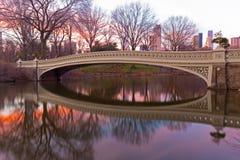 A ponte da curva no nascer do sol bonito no Central Park, New York City do inverno foto de stock