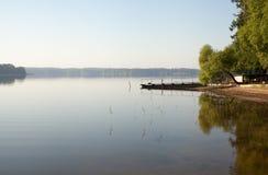 Ponte da pesca na costa de um lago da floresta no amanhecer na névoa imagem de stock royalty free