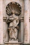 A ponte da saia Estátua antiga próxima do homem com o cordeiro que encontra-se no livro na fachada de St Peter Church Foto de Stock Royalty Free