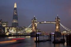 A ponte da torre e o estilhaço em Londres na noite com tráfego arrastam Fotos de Stock Royalty Free