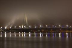Ponte de cabo em Riga através do Daugava do rio Com uma névoa forte visível somente as luzes Imagem de Stock Royalty Free