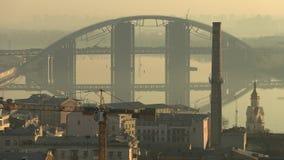 Ponte de Darnystkyibriedge com arquitetura da cidade em Kiev, Ucrânia durante a manhã enevoada com reflexão, vídeo da metragem 4k video estoque