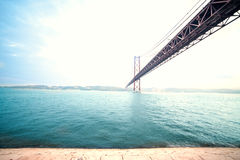 A ponte de 25 de abril sobre o monumento de Tagus River e de Cristo em L Imagens de Stock Royalty Free