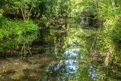 Ponte de madeira arqueada sobre a lagoa do jardim decorativo imagem de stock