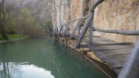Ponte de madeira assustador e perigosa sobre um rio video estoque
