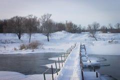 A ponte de madeira através do rio pequeno coberto com a neve Imagem de Stock Royalty Free