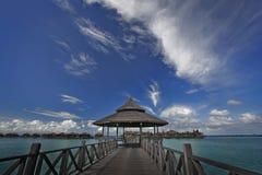 A ponte de madeira conduz ao recurso tropical Imagens de Stock Royalty Free