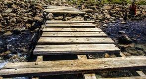 Ponte de madeira do pé em um córrego do rio montanhoso com rochas do seixo e água azul foto de stock