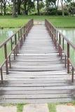 Ponte de madeira do pé no parque com árvores Imagens de Stock