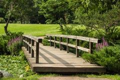 Ponte de madeira no jardim japonês através do arco dos ramos imagens de stock