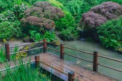 Ponte de madeira sobre a água entre árvores no jardim japonês de Portland, Portland, Oregon imagem de stock royalty free