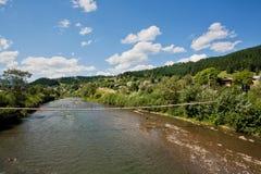 Ponte de madeira suspendida sobre um rio da montanha Fotos de Stock Royalty Free