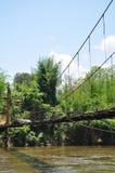 Ponte de madeira suspendida sobre um rio que conduz a uma selva em Tailândia imagem de stock royalty free