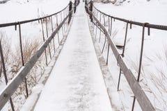 A ponte de madeira velha coberto de neve estreita sobre o rio congelado do inverno fotos de stock royalty free