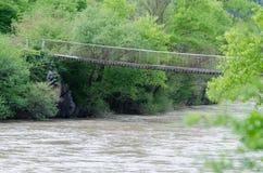 Ponte de madeira velha sobre o rio da montanha da inundação em Geórgia Imagem de Stock