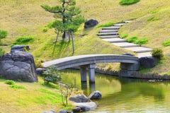 Ponte de pedra cinzenta em um jardim montanhoso rochoso com pinheiro imagens de stock