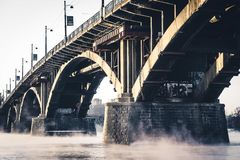 A ponte de pedra no rio enevoado foto de stock royalty free