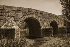 A ponte de pedra romana velha sobre separa o rio em Portagem foto de stock