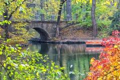 Ponte de pedra sobre a água no parque do outono foto de stock