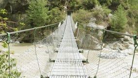 Ponte de suspensão sobre o rio nas montanhas de Nepal Passeio na montanha do circuito de Manaslu video estoque