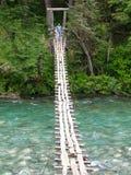 Ponte de suspensão sobre um rio azul fotografia de stock