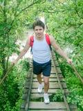 Ponte del baldacchino e zainhi d'uso dell'uomo sull'incrocio della passerella Immagini Stock