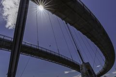 Modern suspended bridge with plane in background Royalty Free Stock Images