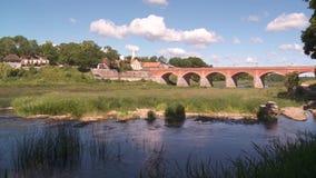 Ponte del mattone attraverso il fiume Venta nella città di Kuldiga video d archivio