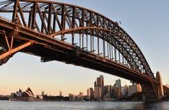 Ponte del porto e del teatro dell'opera dal molo del traghetto del punto di Milsons al tramonto Fotografie Stock Libere da Diritti