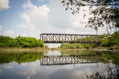 Ponte del treno riflesso nel fiume fotografia stock