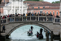 Ponte della Paglia bridge in Venice, Italy. VENICE, ITALY - MAY 1 2016: Ponte della Paglia bridge in Venice, filled with tourists, with the facade of the Church Royalty Free Stock Photo