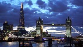 Ponte della torre di Londra ed il coccio al tramonto, cielo nuvoloso scuro blu, costruzioni del fulmine, nave che passa, città ma stock footage