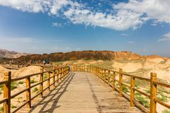 Ponte di cavalletto lungo nel parco di Danxia, sbocciare bianco delle nuvole del cielo fotografia stock