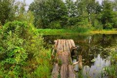 Ponte di legno alle quiete, piccolo fiume Fotografia Stock