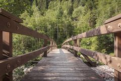 Ponte di legno che attraversa un fiume nelle montagne della Svizzera fotografie stock libere da diritti