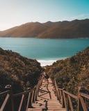 Ponte di legno della scala che conduce giù alla bella spiaggia sabbiosa con la gente su  fotografia stock libera da diritti