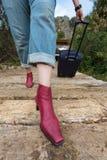 Ponte di legno di camminata della persona che tira le scarpe della valigia di viaggio vicino su Fotografia Stock