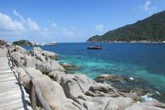 Ponte di legno e grandi rocce sulla costa di mare fotografia stock libera da diritti