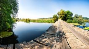Ponte di legno sopra il fiume con gli alberi verdi sulla riva fotografia stock libera da diritti