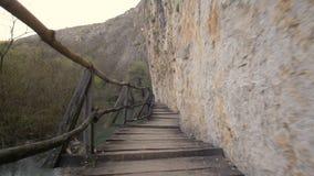 Ponte di legno spaventoso e pericoloso sopra un fiume video d archivio