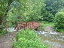 Ponte di legno sul fiume della montagna Fotografie Stock