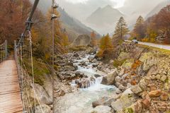 Ponte di legno sul fiume e sul panorama della montagna fotografie stock