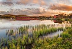 Ponte di legno sul lago Narsjoen in Norvegia al tramonto Fotografia Stock