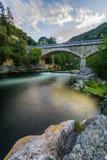 Ponte di pietra, fiume variopinto & nuvole fotografia stock