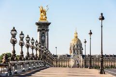 Ponte di Pont Alexandre III sopra il fiume la Senna ed il DES Invalides dell'hotel nei precedenti nella mattina soleggiata di est fotografia stock