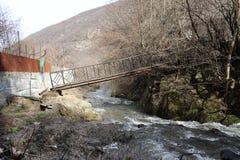 Ponte di stupore sopra un fiume della montagna fotografia stock libera da diritti