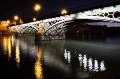 Ponte di Triana sopra il fiume di Guadalquivir al tramonto con il refle del fiume immagini stock