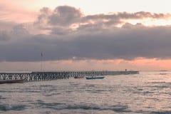 Ponte do cais na praia no por do sol fotografia de stock